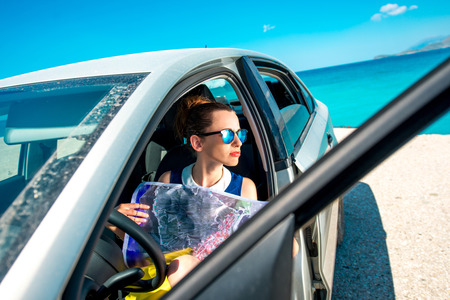 where to go: Young woman traveler sitting with paper map in the car and looking where to go on blue sea background