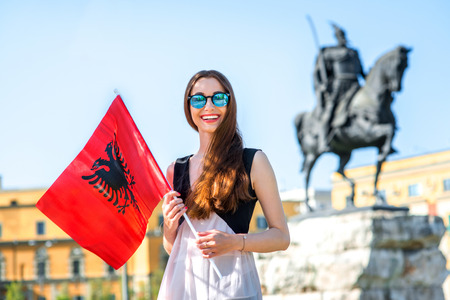 Young Albanian patriot standing with flag in the center of Tirana city, Albania