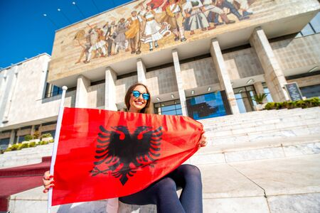 albanian: Young woman patriot with Albanian flag sitting in front of National museum in Tirana city