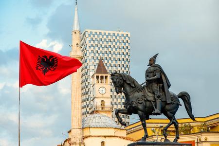 Skanderbegmonument met vlag, moskee en klokkentoren op de achtergrond in het centrum van de stad Tirana, Albanië. Stockfoto