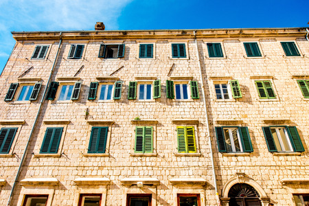 many windows: Ancient building with many windows and green shutters in Kotor old city, Montenegro