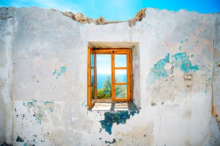 바다에서 아름 다운 경치와 함께 버려진 된 집에서 오래 된 창 스톡 콘텐츠