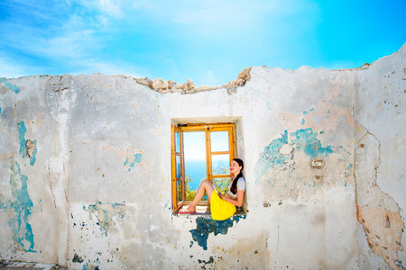 Young woman sitting on the window with sea view in abandoned house photo