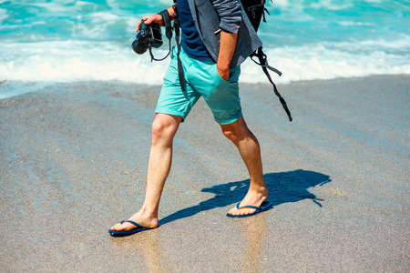 photographers: Man in shorts walking with photo camera on the beach Stock Photo