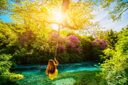 Happy young woman swinging with bungee above the river in the forest