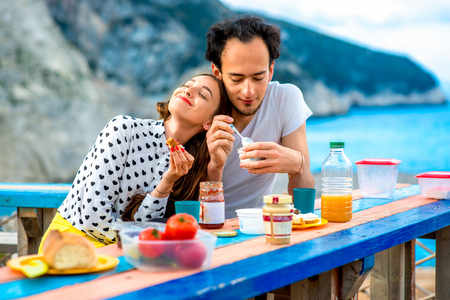 eating yogurt: Young couple eating breakfast on the table near the sea on their summer vacation