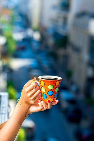 blured: Woman holding colorful coffee cup on blured city street background. Stock Photo