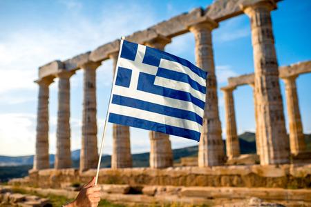 スニオン、ギリシャのポセイドン神殿の背景にギリシャ国旗