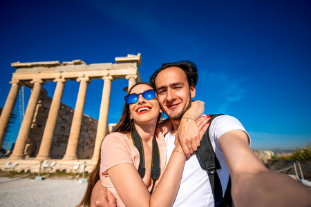 classical greece: Young couple travelers taking selfie picture with Erechtheum temple on background in Acropolis in Athens, Greece Stock Photo