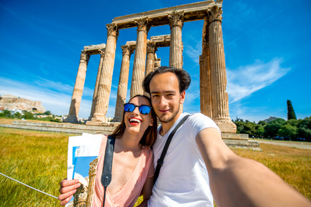 Young couple traveler taking selfie picture with Zeus temple on background in Acropolis, Greece photo