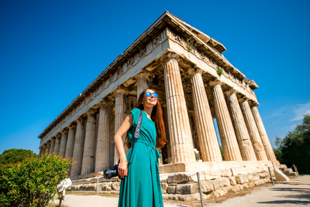 Woman with photo camera near Hephaistos temple in Agora near Acropolis in Athens, Greece