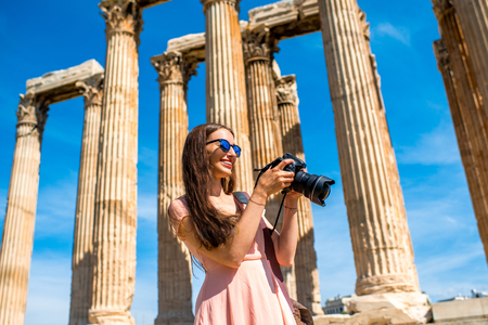 olympian: Young and smiling woman photographer taking picture with professional camera of Zeus temple in Acropolis