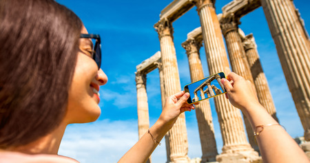 Young woman photographing with smart phone Zeus temple in Greece photo
