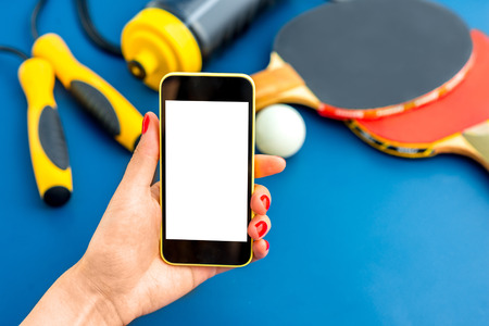 Using smartphone with white screen on table with table tennis rackets, rope and drink bottle on background photo