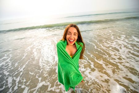 sexy woman standing: Young woman covered in green towel having fun on the beach