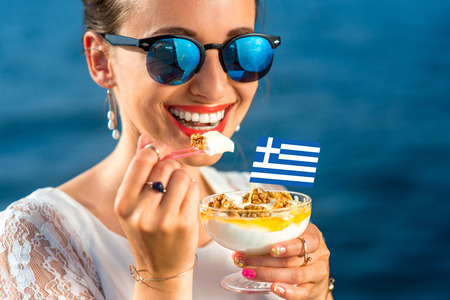 yogur: Sonriente mujer comer yogur griego tradicional con nueces y miel al aire libre en fondo azul del mar