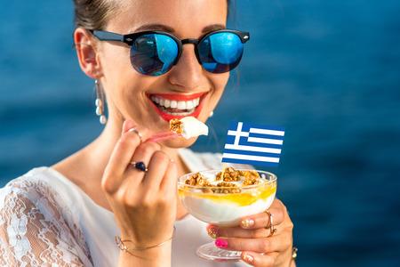 yaourt: Sourire, femme, manger du yogourt grec traditionnel avec des noix et de miel en plein air sur la mer bleu fond Banque d'images