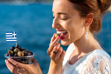 Smiling woman eating fresh green and black olives with greek flag outdoors on blue sea background Stock Photo