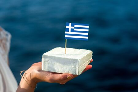 haloumi: Holding in hand traditional greek feta cheese with greek flag on blue sea background Stock Photo