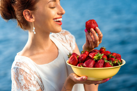 Woman eating fresh strawberry from a big yellow plate outdoors on the blue sea background