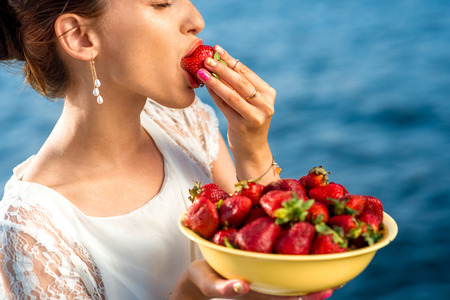 personen: Vrouw het eten van verse aardbeien uit een grote gele bord buiten op de blauwe zee achtergrond