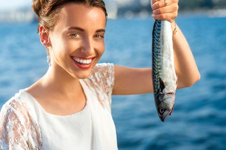 Jonge vrouw die verse vis buiten op zee achtergrond