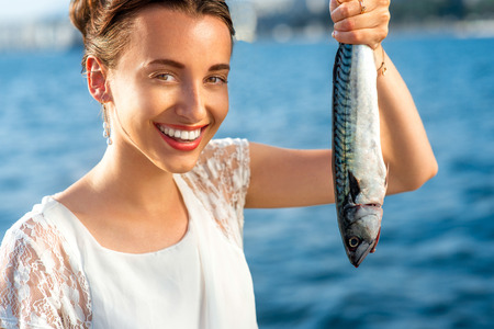 catch of fish: Young woman holding fresh fish outdoors on sea background