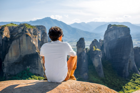 Well-dressed man sitting on the rocky mountain on beautiful scenic clif background near Meteora monasteries in Greece. Back view.