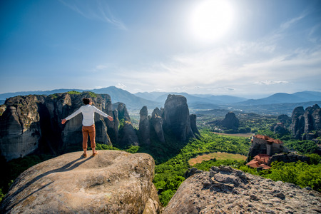 Well-dressed man sitting on the rocky mountain on beautiful scenic clif background near Meteora monasteries in Greece. Back view, General plan.