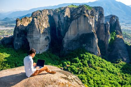 Hombre de trabajo con ordenador portátil sentado en la montaña rocosa en el fondo hermoso clif escénica cerca de los monasterios de Meteora en Grecia Elegante. Volver la vista, el plan general.