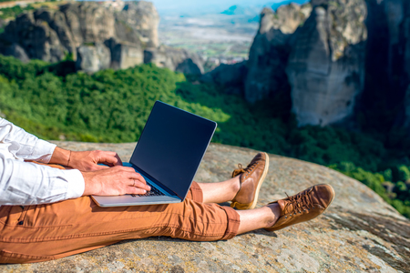Well-dressed man working with laptop sitting on the rocky mountain on beautiful scenic clif background. Close up view with no face focused on laptop with hands