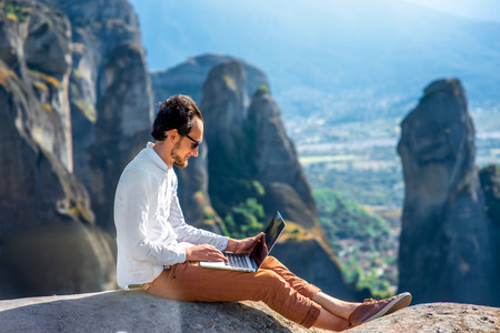 Well-dressed man working with laptop sitting on the rocky mountain on beautiful scenic clif background near Meteora monasteries in Greece.