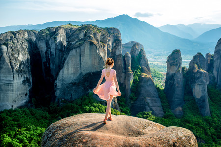 monasteries: Young woman in pink dress enjoying nature on the mountains near Meteora monasteries in Greece Stock Photo