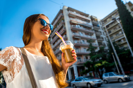 fredo: Young woman walking on the street with take away coffee  in the transparent cup in the city