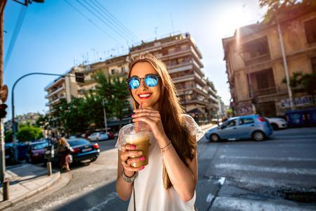 fredo: Giovane donna che cammina per strada con take away caffè in tazza trasparente in città Archivio Fotografico