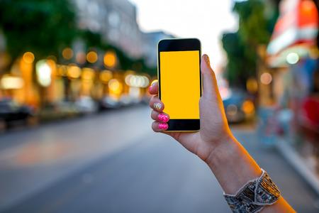 다채로운 나뭇잎 배경으로 거리의 저녁 빛에 빈 화면으로 모바일 스마트 휴대 전화를 사용하는 여자 손 스톡 콘텐츠