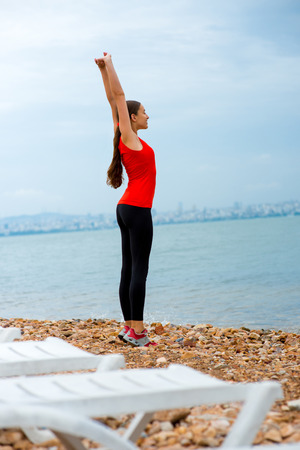 istanbul beach: Young woman having exercise on the beach on the sea and city background in cloudy weather