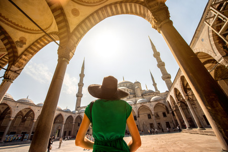 Young woman traveler in black hat and green dress looking on amazing Blue Mosque in Istanbul, Turkey Foto de archivo