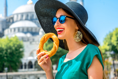 sesame street: Young woman eating turkish bagel in Istanbul, Turkey. Traditional turkish street food.
