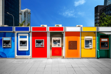 Cashpoint with colorful bankomats in the modern city photo