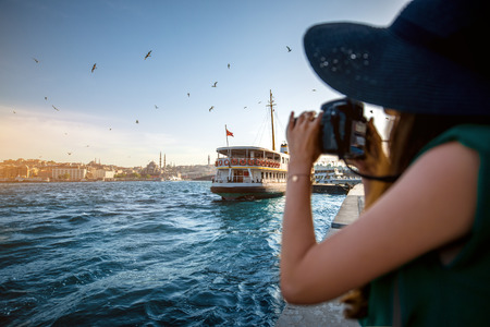 Young woman traveler in green dress and hat enjoying great view of the Bosphorus in Istanbul