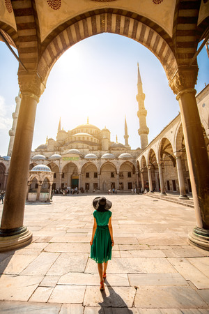 Young woman traveler in the green dress and hat walking to the Blue Mosque in Istanbul