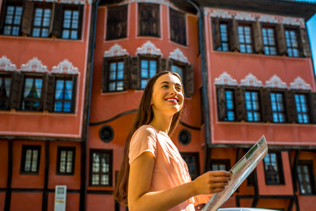 Young woman traveling with map in Plovdiv old city center in Bulgaria