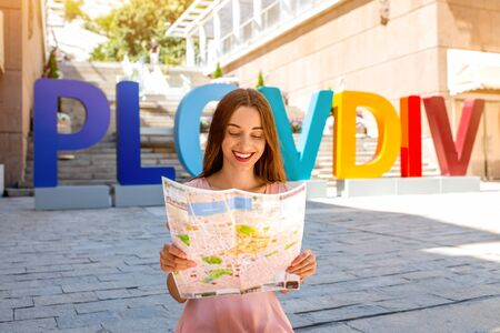 bulgaria girl: Woman with travel map on colorful letters background in Plovdiv, european cultural capital 2019