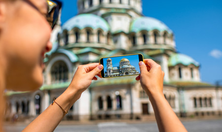 Woman tourist photographing with smart phone the St. Alexander Nevsky Cathedral in Sofia, the capital of Bulgaria Stok Fotoğraf