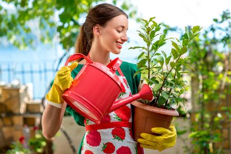 Jonge vrouw in schort en werkhandschoenen de zorg voor de bloem in in de tuin Stockfoto