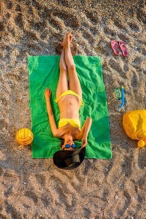 toallas: Mujer en traje de ba�o y sombrero que miente en la toalla verde en la playa. Vista superior Foto de archivo
