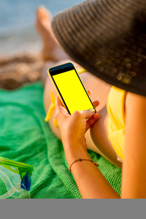 Young woman in swimsuit using mobile phone with empty screen for copy paste lying on the green towel on the beach. Top view focused on the hand with phone. Stock Photo