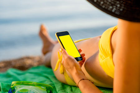copy paste: Young woman in swimsuit using mobile phone with empty screen for copy paste lying on the green towel on the beach. Focused on the hand with phone.