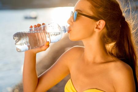 tomando agua: Mujer joven que bebe agua con gas de la botella transparente en la playa en la puesta del sol
